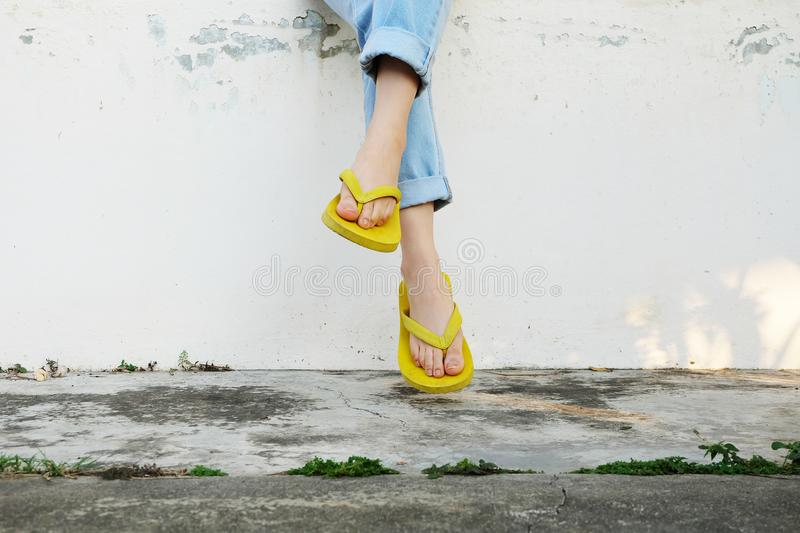 Yellow Sandals. Woman Wearing Flip Flops and Blue Jeans Standing on Old Cement Floor. Background Great for Any Use royalty free stock photography