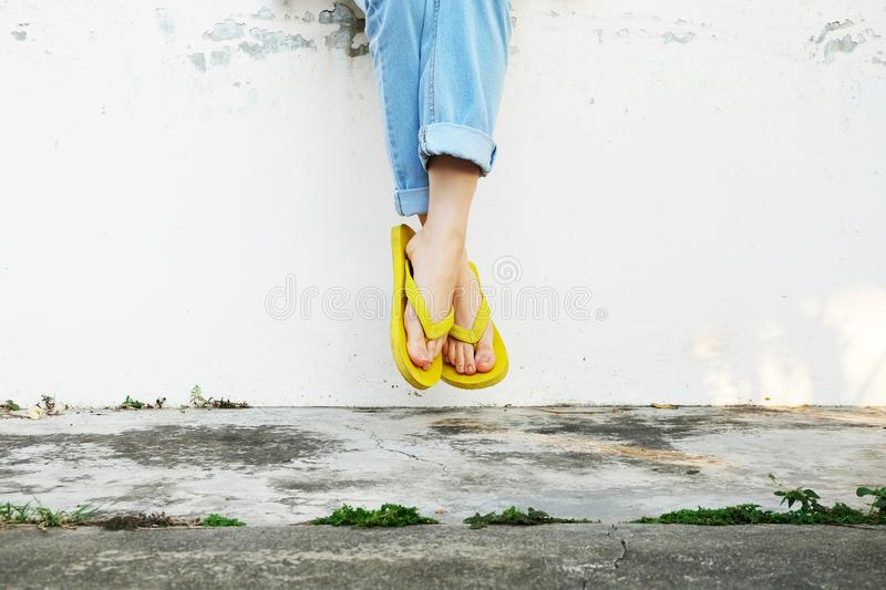 Yellow Sandals. Woman Wearing Flip Flops and Blue Jeans Standing on Old Cement Floor. Background Great for Any Use royalty free stock photos
