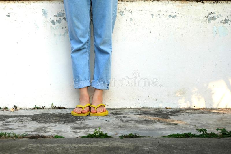 Yellow Sandals. Woman Wearing Flip Flops and Blue Jeans Standing on Old Cement Floor. Background Great for Any Use royalty free stock photo