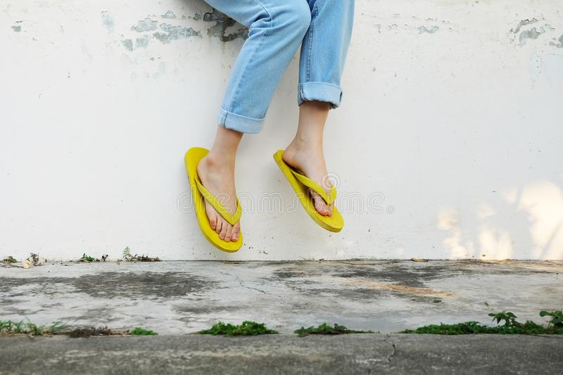Yellow Sandals. Woman Wearing Flip Flops and Blue Jeans Standing on Old Cement Floor. Background Great for Any Use stock images