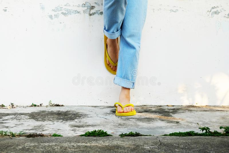 Yellow Sandals. Woman Wearing Flip Flops and Blue Jeans Standing on Old Cement Floor. Background Great for Any Use stock image