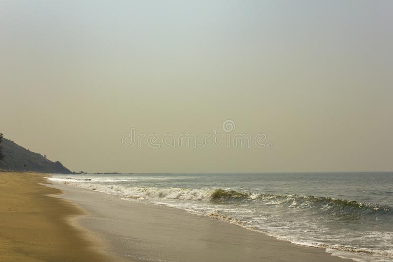 Yellow sandy beach on the background of the ocean with waves under a clear sky. A yellow sandy beach on the background of the ocean with waves under a clear sky royalty free stock image