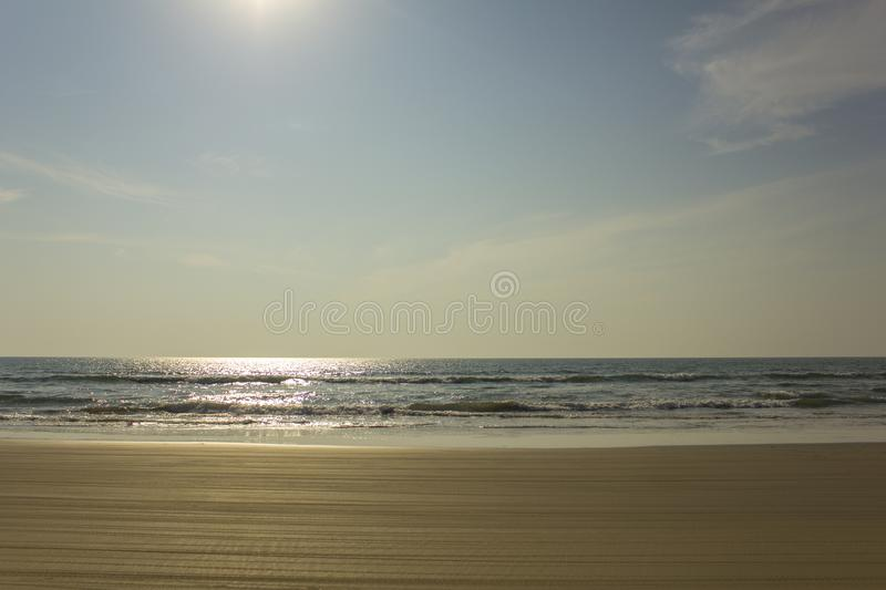 Yellow sandy beach with motorcycle tire tracks against the backdrop of sea waves under a clear blue sky with the sun. A yellow sandy beach with motorcycle tire royalty free stock images