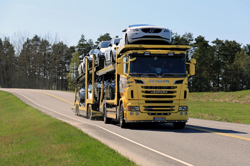 Yellow Scania Car Carrier Transports New Cars on Spring Road. SALO, FINLAND - MAY 8, 2016: Yellow Scania R500 truck hauls a load of new cars along hiighway in stock image