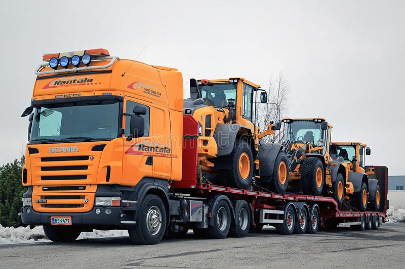 Yellow Scania Hauls Long Load. LIETO, FINLAND - MARCH 12, 2016: Scania R500 V8 truck is ready to haul three Volvo L60H wheel loaders. The operating weight of stock photography