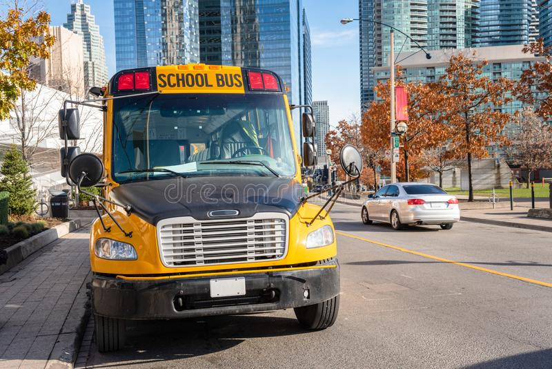 Yellow School Bus Parked along a Street on a Sunny Autumn Morning stock image