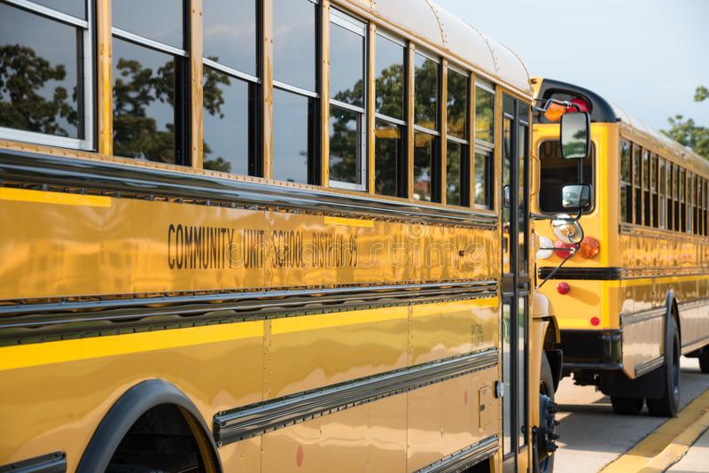 Yellow school buses along curb royalty free stock photo