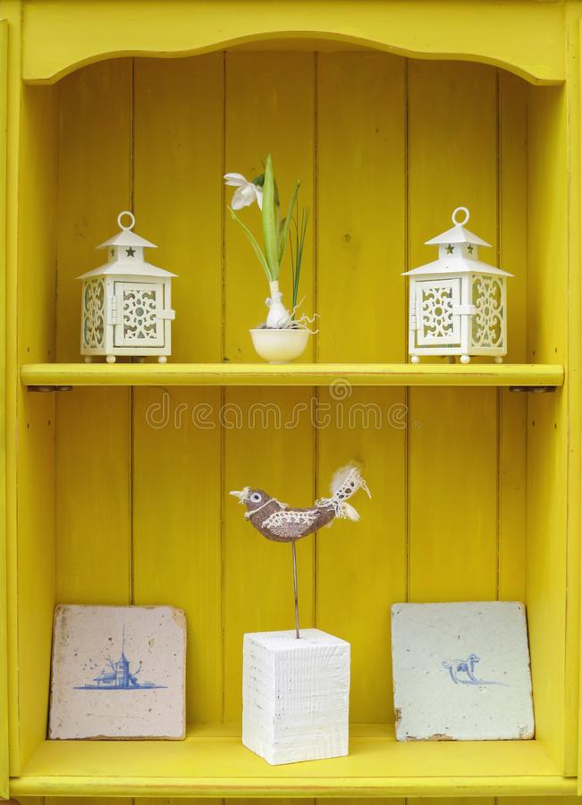 Yellow shabby chic interior design display. Dresser shelf ornaments. Interior design display. Close up detail of yellow shabby chic Welsh dresser shelves with stock photos