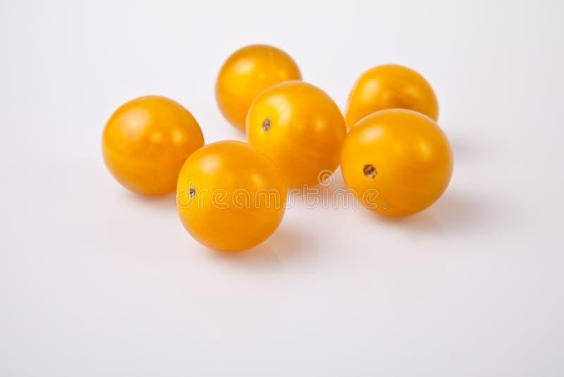 Yellow shiny cherry tomatoes. Isolated over white background stock photos