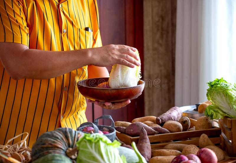 Yellow shirt chef man select the ingredient and raw material for his cook of that day by select various vegetables in his kitchen stock photos