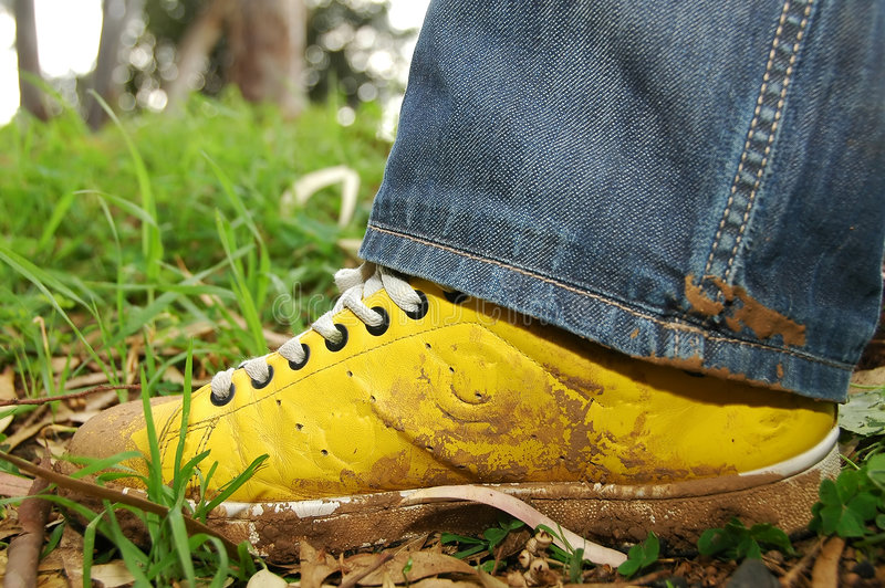 Yellow shoes full of mud stock image