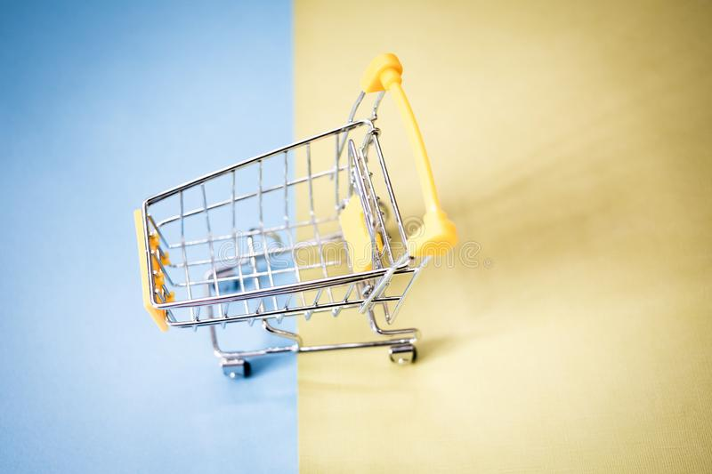 Yellow shopping cart. Background, basket, black, business, buy, carry, color, commerce, commercial, concept, consumer, consumerism, container, customer, design royalty free stock photos