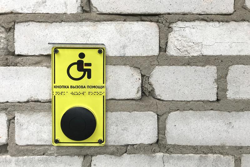 Yellow sign with help button calling for disabled people, Braille blind duplication. Close up of a yellow sign calling for help for disabled people on a brick stock photos