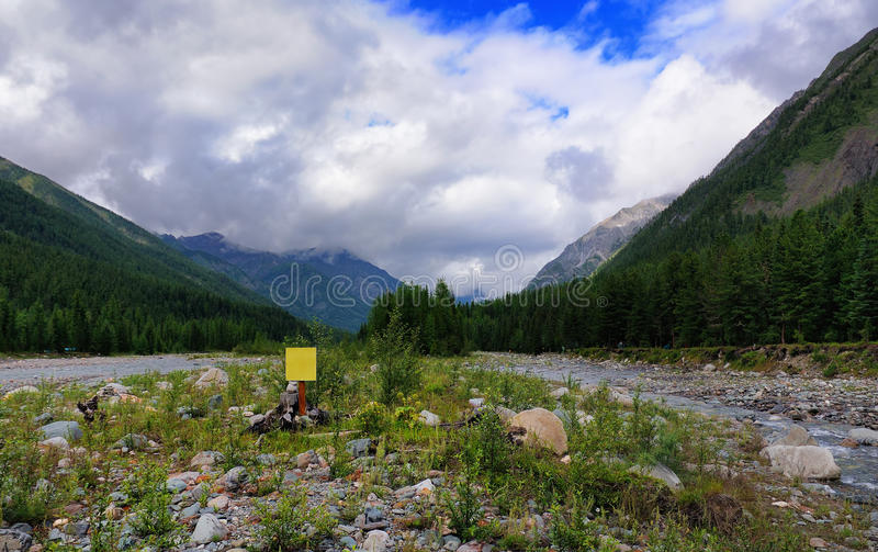Yellow sign in line with the mountain river. Yellow square sign in line with the mountain river. Shumak river. Eastern Sayan. Republic of Buryatia stock image