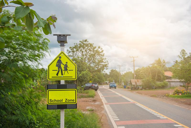 Yellow sign school zone symbol in the countryside stock photo