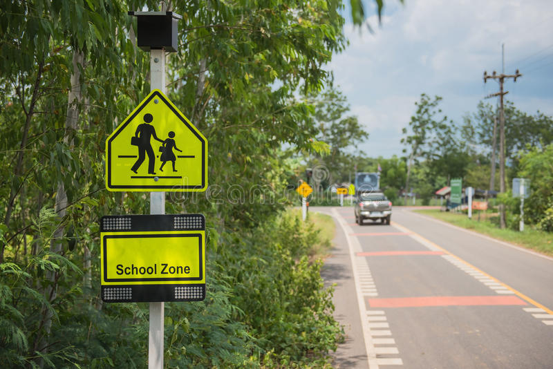 Yellow sign school zone symbol in the countryside stock image