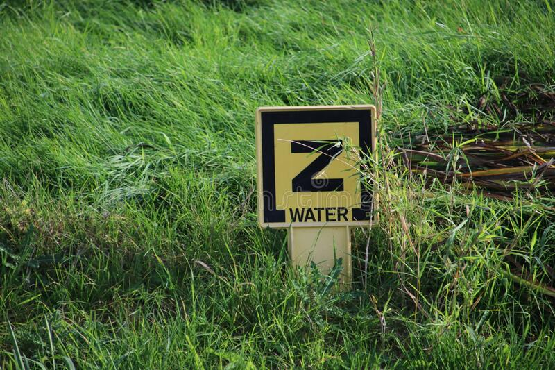 Yellow sign with a Z and water on it to warn for a sunken pipe for water supply in the ditch royalty free stock images