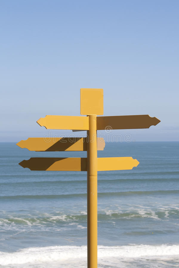 Yellow signpost near ocean royalty free stock image