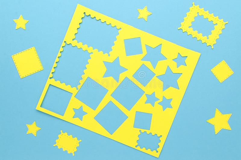 Yellow simple shapes cut from paper. On blue background royalty free stock images