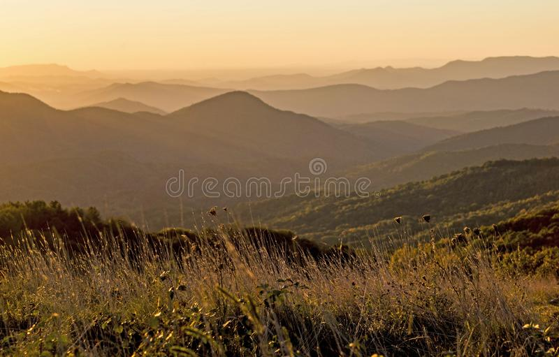 Yellow Mountaintop layers as the sun drops below the skyline. stock photos