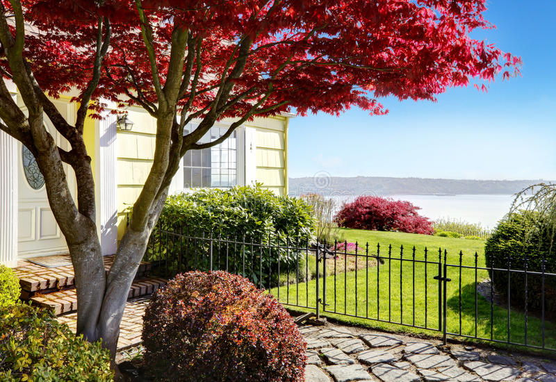 Yellow small home with water view and red maple. Entrance with metal fence royalty free stock photography