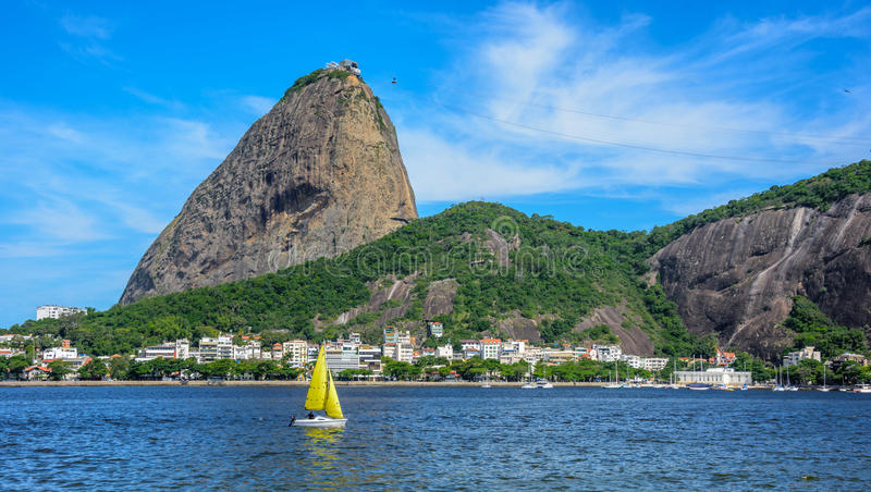 Yellow small sailing yacht, Sugarloaf Mountain and Botafogo Bay in Rio de Janeiro royalty free stock photography