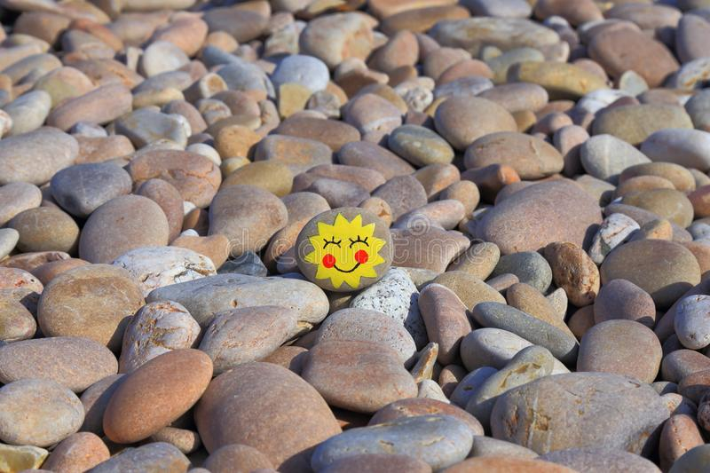 Yellow smiley face painted on the stone. Pebble beach on the Jurassic Coast in Devon royalty free stock image