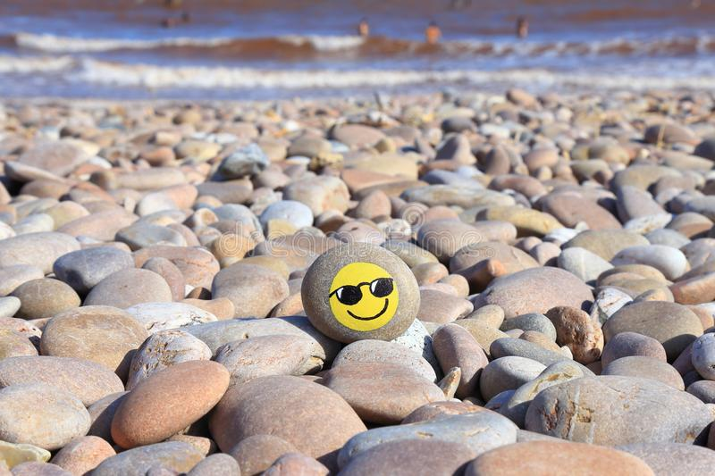 Yellow smiley face painted on the stone. Pebble beach on the Jurassic Coast in Devon stock photography