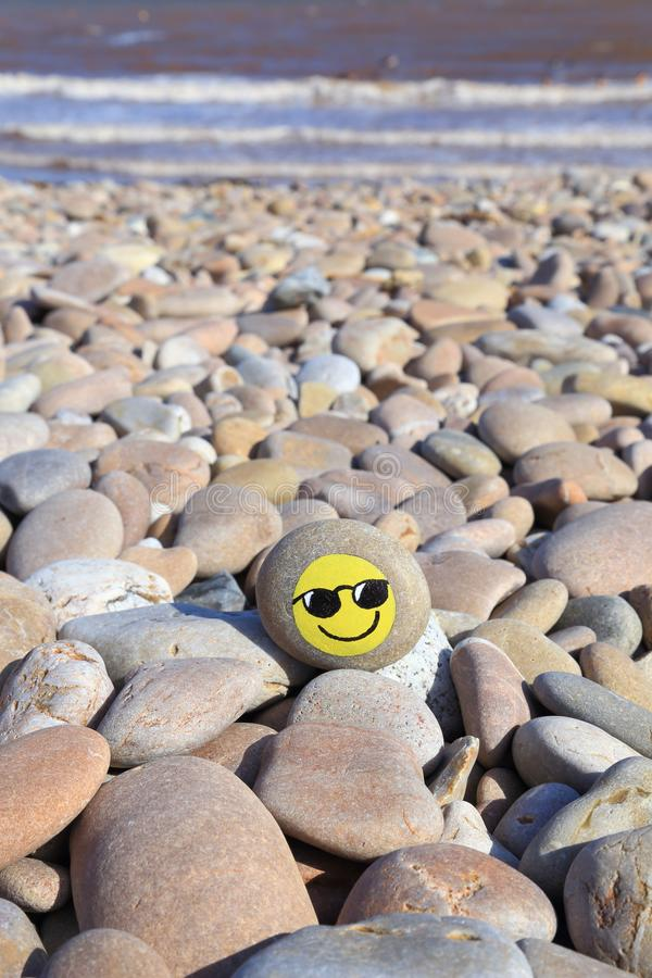 Yellow smiley face painted on the stone. Pebble beach on the Jurassic Coast in Devon stock image