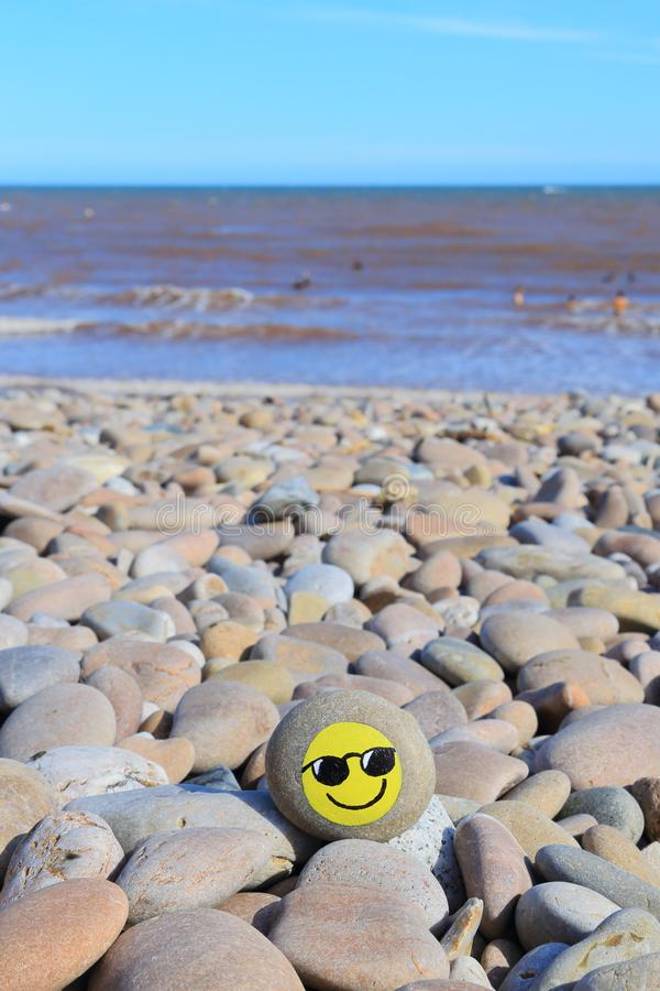 Yellow smiley face painted on the stone. Pebble beach on the Jurassic Coast in Devon stock photo