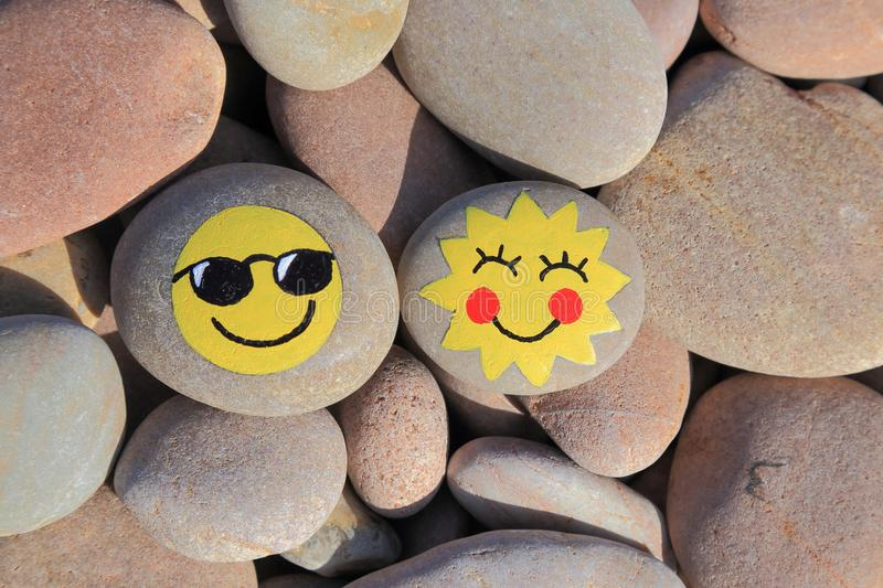 Yellow smiley face painted on the stone. Pebble beach on the Jurassic Coast in Devon royalty free stock photography