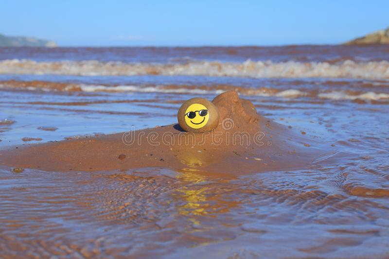 Yellow smiley face painted on the stone. Sandy beach on the Jurassic Coast in Devon royalty free stock image