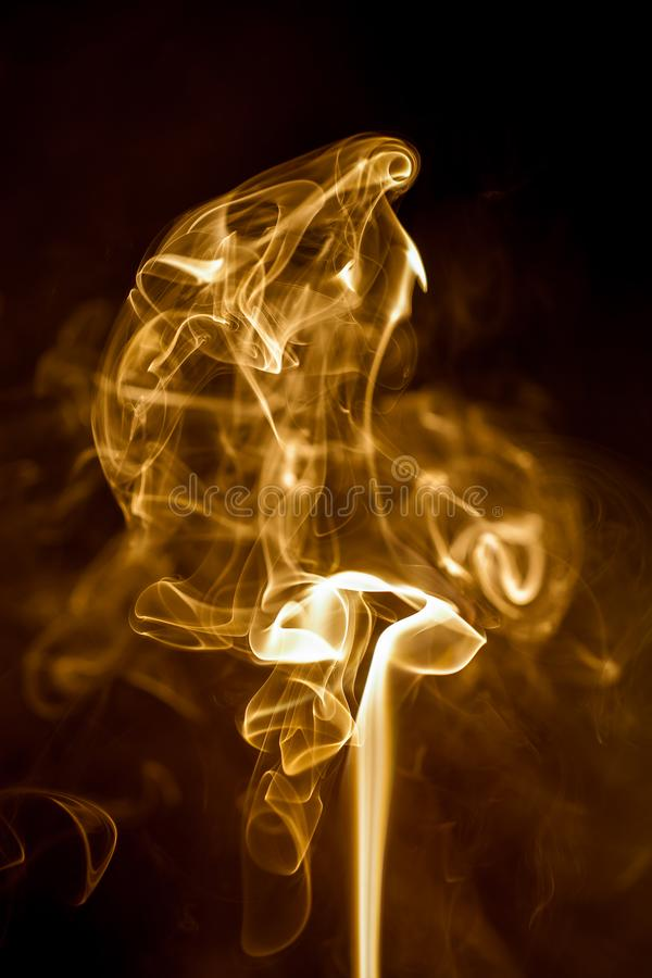 Yellow smoke on black background. Abstract, art, backdrop, color, concept, curve, design, effect, fire, graphic, light, motion, pattern, shape, smooth, swirl stock images