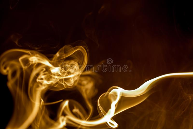 Yellow smoke on black background. Abstract, art, backdrop, color, concept, curve, design, effect, fire, graphic, light, motion, pattern, shape, smooth, swirl stock image