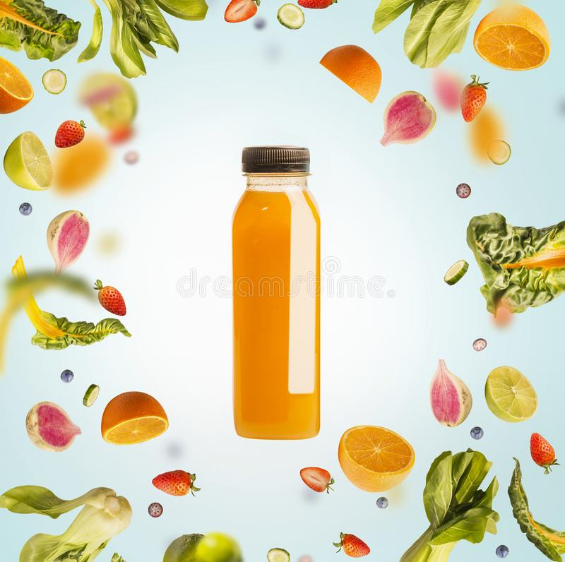 Yellow smoothie or juice bottle with flying or falling ingredients: citrus fruits, oranges and berries on light blue background royalty free stock images