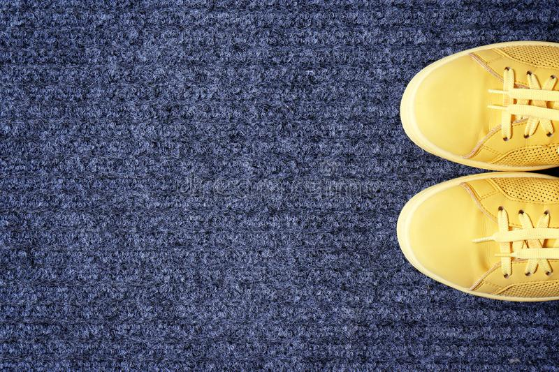 Yellow sneakers on gray doormat, top view. Space for text stock photos