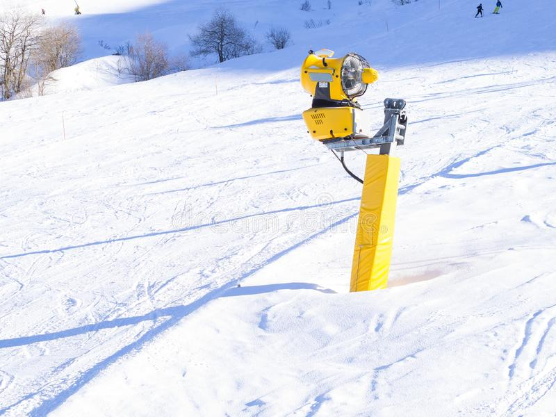 Yellow snow cannon on the ski slopes. Artificial snow making machine royalty free stock images