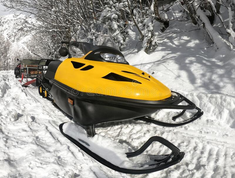 Yellow snowmobile on white snow. Front view of yellow snowmobile on snow at winter sunny day stock images