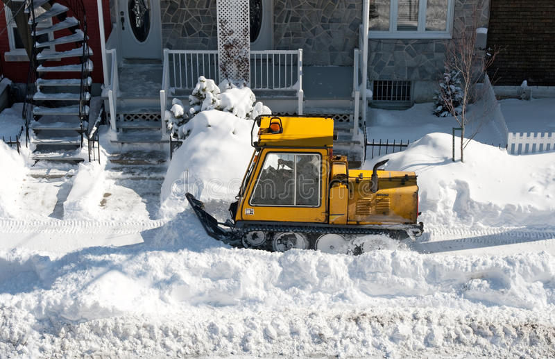 Yellow snowplough removing snow in the city stock images