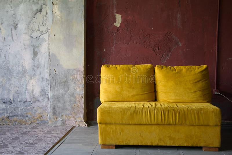 Yellow sofa over red brick wall in a loft style studio, minimalism furniture concept, photo studio interior stock images