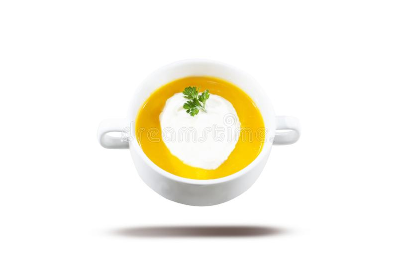 Yellow Soup on white bowl. Pumpkin and carrot soup, served with cream and parsley. Isolated on white background royalty free stock image