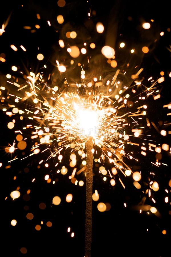 Yellow sparkler with fire particles stock photos