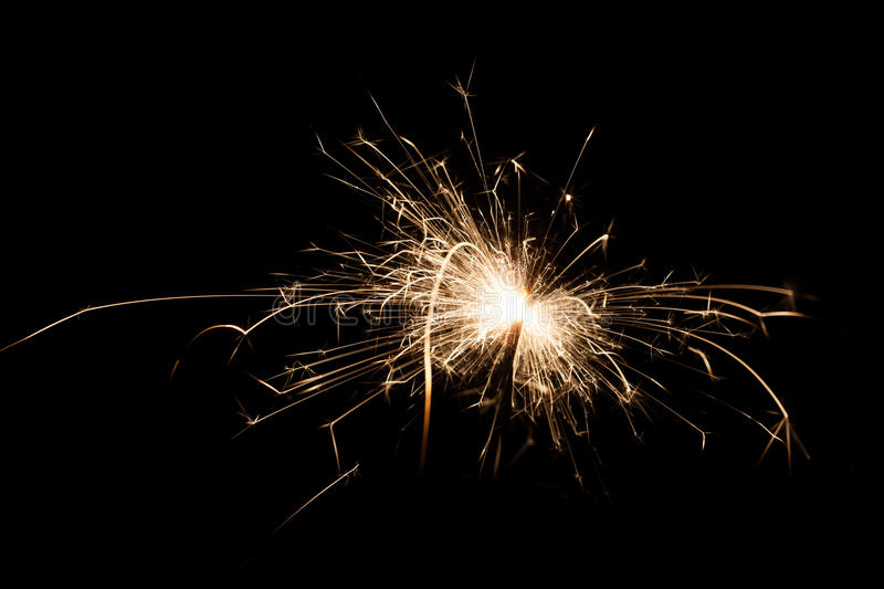 Yellow sparkler on isolated black color background. stock photos