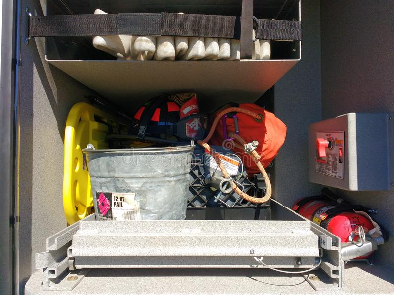Firefighting Equipment in a Fire Truck, Rutherford, NJ, USA. A yellow spine board, hose, bucket, fire extinguisher, and firefighter`s helmet are among the gear royalty free stock images