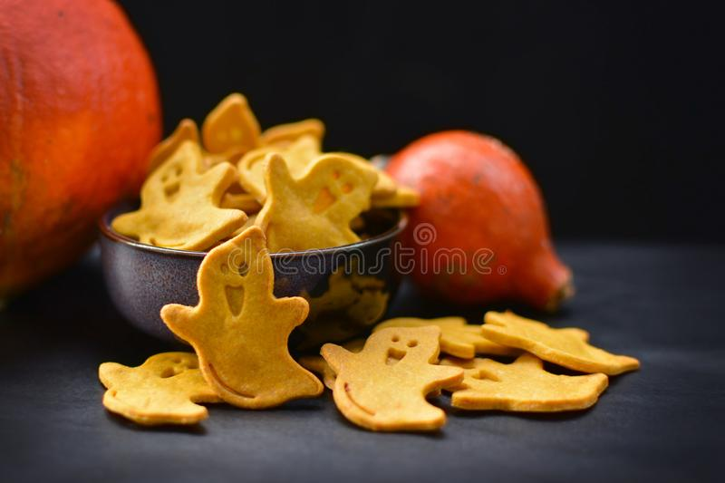 Yellow spooky ghost shaped Halloween cookies with orange pumpkins on dark background stock photo