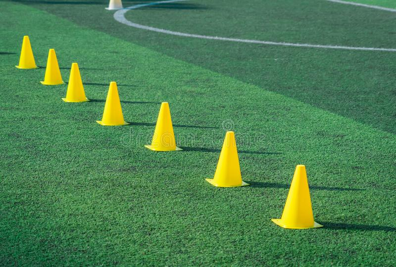 Yellow sport cones marker on soccer green grass pitch for children football training session royalty free stock photography