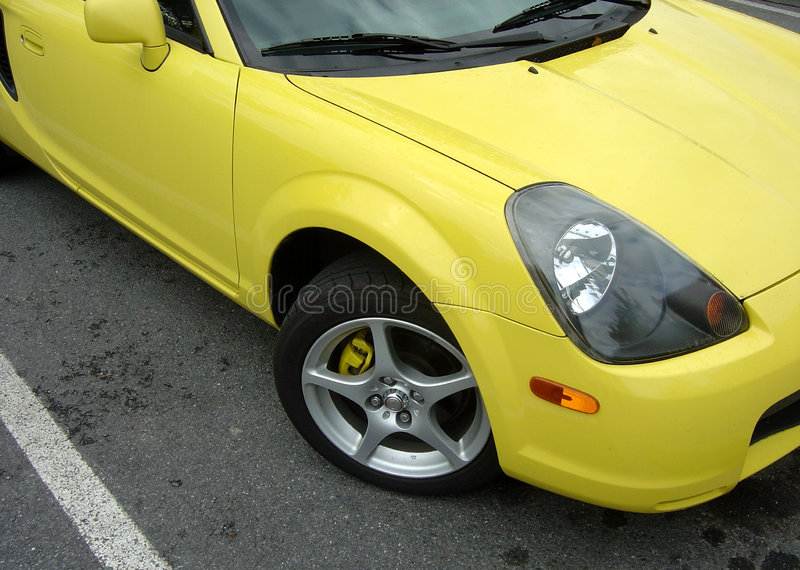 Yellow Sports Car. A yellow sports car sitting in a parking space stock image