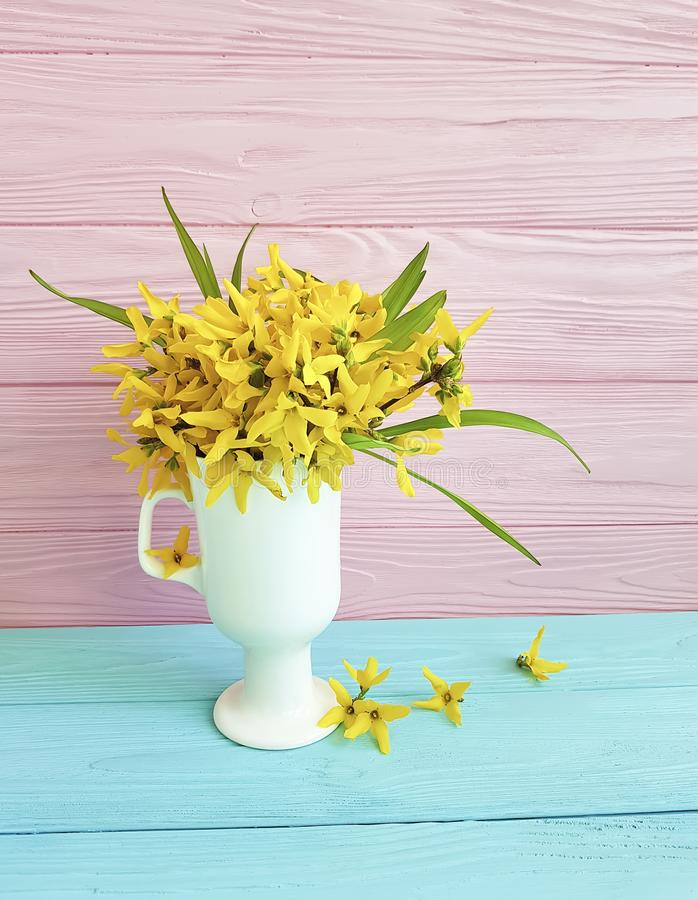 Yellow spring flowers bouquet blooming in a vase on a colored wooden background royalty free stock photo
