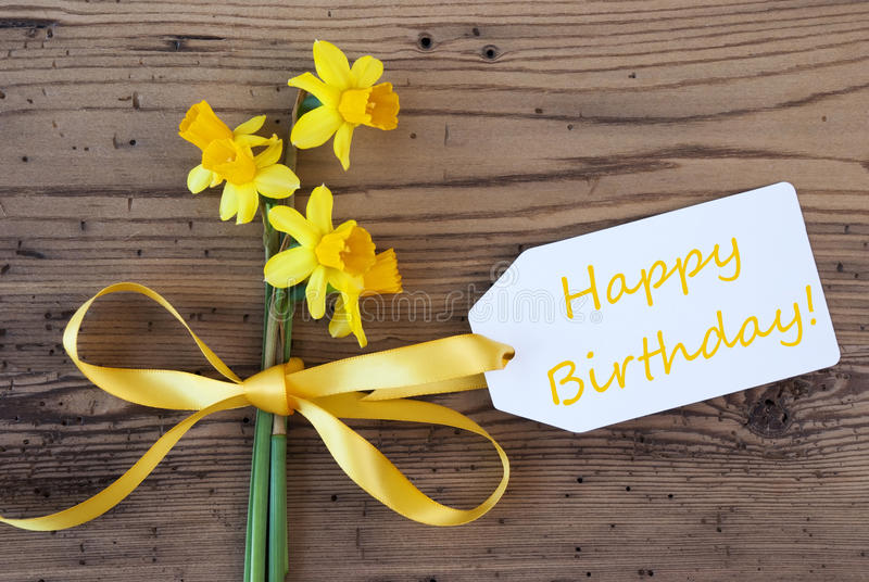 Yellow Spring Narcissus, Label, Text Happy Birthday. Label With English Text Happy Birthday. Yellow Spring Narcissus Or Daffodil With Ribbon. Aged, Rustic Wodden royalty free stock images
