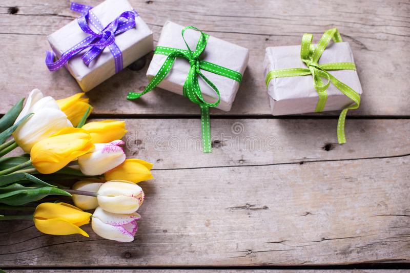Yellow spring tulips and box with presents on wooden backgroun. D. Selective focus is on flowers. Place for text stock photography